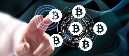 Woman touching a bitcoin concept on a touch screen with her finger 写真素材