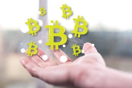 Bitcoin concept above a hand of a man Фото со стока