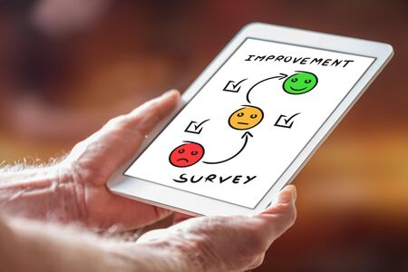 Man holding a tablet showing survey concept Stock Photo
