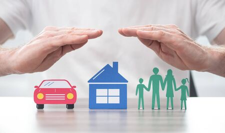 Family, house and car protected by hands - Concept of life, home and auto insurance Foto de archivo - 130593419