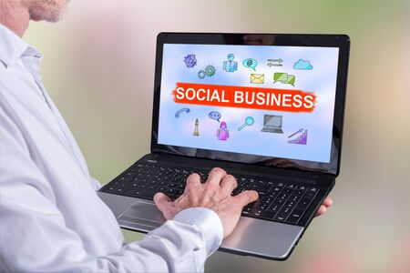 Man using a laptop with social business concept on the screen Stock Photo