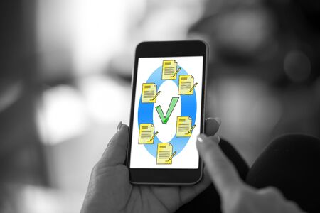 Hand holding a smartphone with document validation concept 스톡 콘텐츠