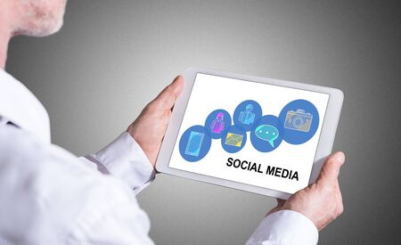 Man holding a tablet showing social media concept Фото со стока