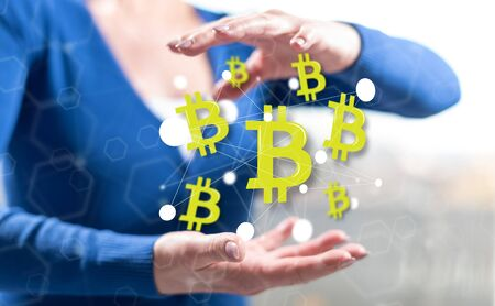 Bitcoin concept between hands of a woman in background