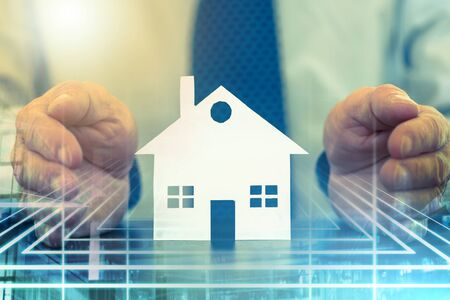 Insurer protecting a house with his hands, color effect; multiple exposure