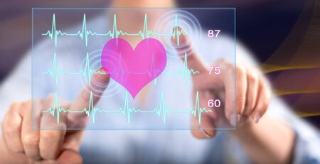 Woman touching a heart beats graph concept on a touch screen with her fingers