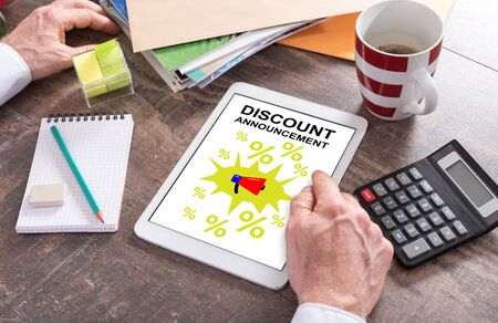 Man using a tablet showing a discount announcement concept Stockfoto