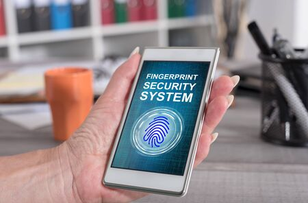 Female hand holding a smartphone with fingerprint security system concept Stock fotó