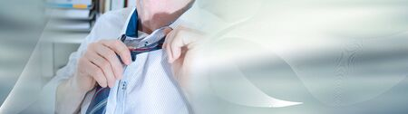 Businessman undoing his tie at office; panoramic banner