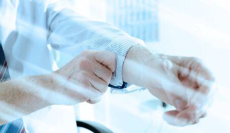 Businessman rolling up his sleeve at office; light effect Standard-Bild