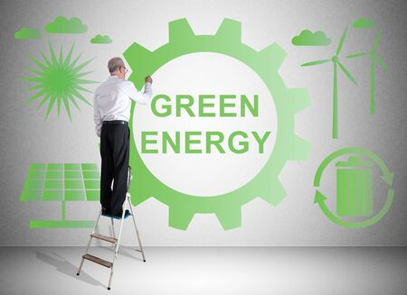 Man on a ladder drawing green energy concept on a wall