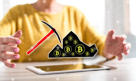 Digital tablet with bitcoin mining concept between hands of a woman in background Stok Fotoğraf