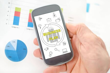 Business plan concept on a smartphone held by a hand Banco de Imagens