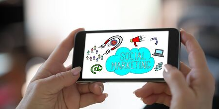 Hand holding a smartphone with social marketing concept