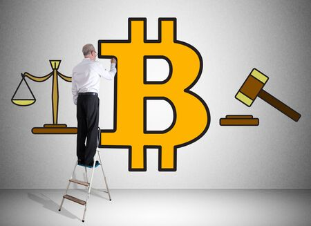 Man on a ladder drawing bitcoin regulation concept on a wall