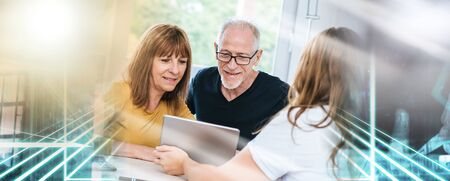Real estate agent giving explanations on tablet to senior couple; multiple exposure