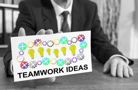 Businessman showing an index card with teamwork idea concept
