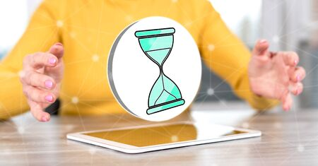 Digital tablet with time management concept between hands of a woman in background