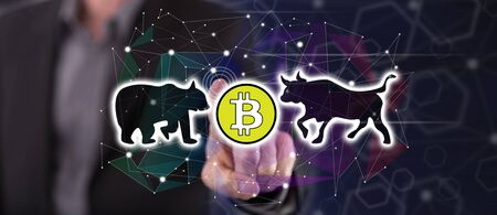 Man touching a bitcoin trend concept on a touch screen with his finger