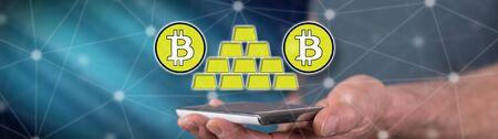 Bitcoin virtual gold concept above a smartphone held by a man Stok Fotoğraf