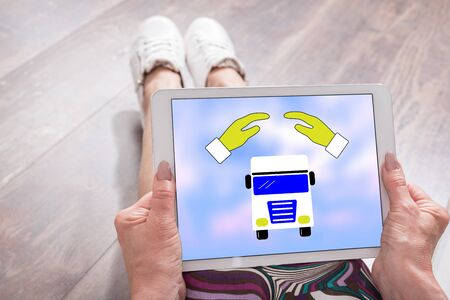 Woman sitting on the floor with a tablet showing truck insurance concept 写真素材
