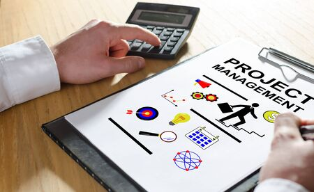 Project management concept with hand using a calculator