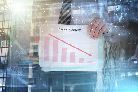 Businessman showing an economic activity falling down; multiple exposure