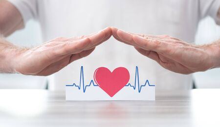 Heartbeat symbol protected by hands - Concept of health insurance Stock Photo