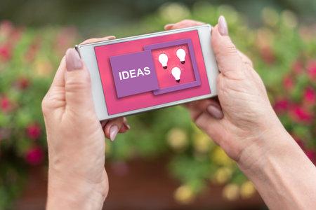 Female hands holding a smartphone with ideas concept Banco de Imagens