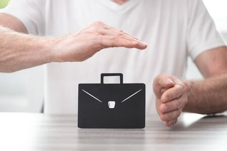 Briefcase protected by hands - Concept of job loss insurance Фото со стока