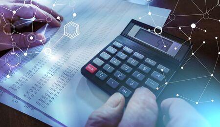 Male hand using calculator for analyze financial data; light effect