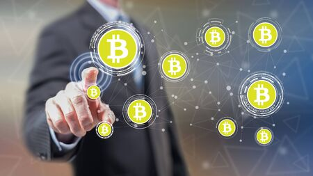 Man touching a bitcoin concept on a touch screen with his fingers