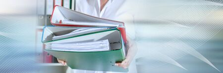 Businesswoman holding binders at office; panoramic banner