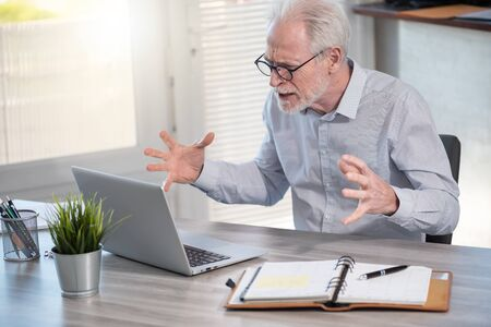 Enraged businessman in front of his laptop