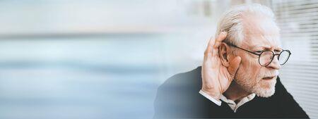 Portret van de hogere mens die gehoorproblemen heeft; panoramische banner