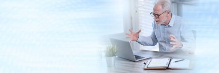 Enraged businessman in front of his laptop; panoramic banner Stock Photo
