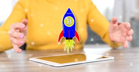 Digital tablet with bitcoin rise concept between hands of a woman in background