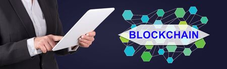 Woman using digital tablet with blockchain concept on background Фото со стока