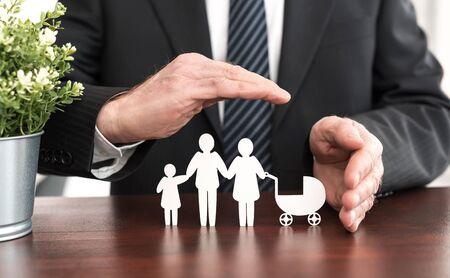 Versicherer, der eine Familie mit seinen Händen schützt