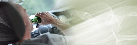 Man drinking a beer while driving; panoramic banner