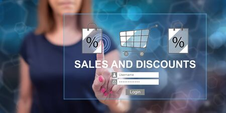 Woman touching a sales and discounts concept on a touch screen with her finger Stock Photo