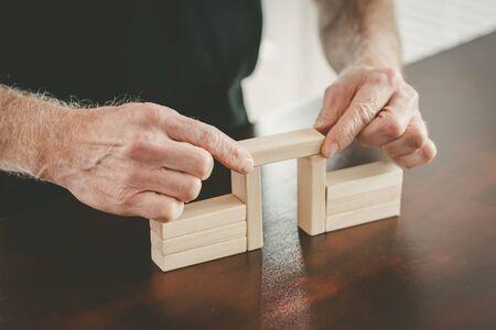 Hands building a wooden block bridge; concept of business association