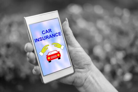 Female hand holding a smartphone with car insurance concept
