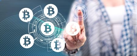 Woman touching a bitcoin concept on a touch screen with her finger Фото со стока