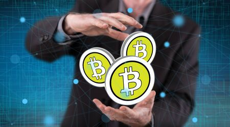 Bitcoin concept between hands of a man in background Фото со стока