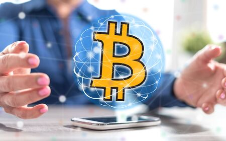Smartphone with bitcoin currency concept between hands of a woman in background