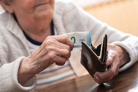 Elderly woman taking out a banknote from her wallet