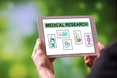 Man holding a tablet showing medical research concept