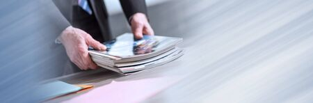 Hands of businessman holding magazines; panoramic banner