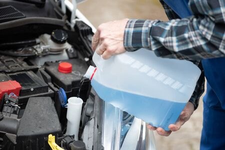 Hands of mechanic pouring blue windshield washer fluid in a car